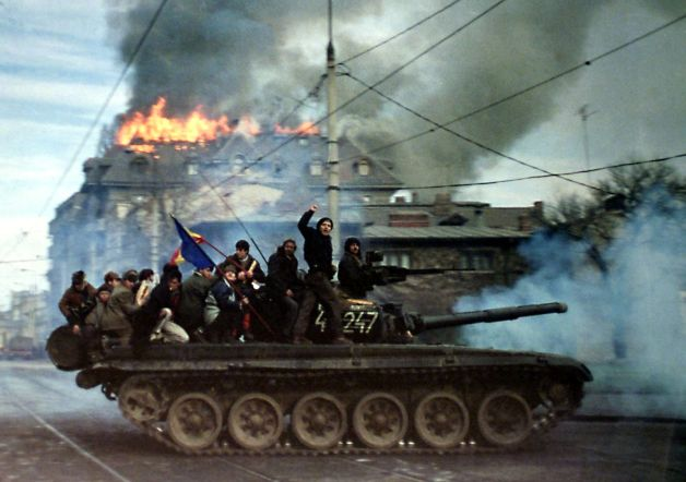 FILE PHOTO 22DEC89 - Romanian demonstrators sit on top of a tank as it passes in front of a burning building, December 22 1989, in Bucharest during the 1989 anti-communist revolution. This month the country celebrates in subdued mood 10 years since the violent uprising, during which dictator Nicolae Ceausescu was toppled and shot on Christmas day 1989. More than 1,000 Romanians were killed across Romania during clashes between demonstrators and Ceausescu's security forces, in what amounted to eastern Europe's most violent anti-communist revolution. RS/